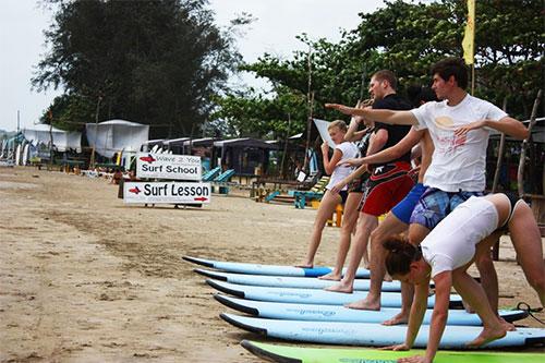 surfers beginners training on the beach